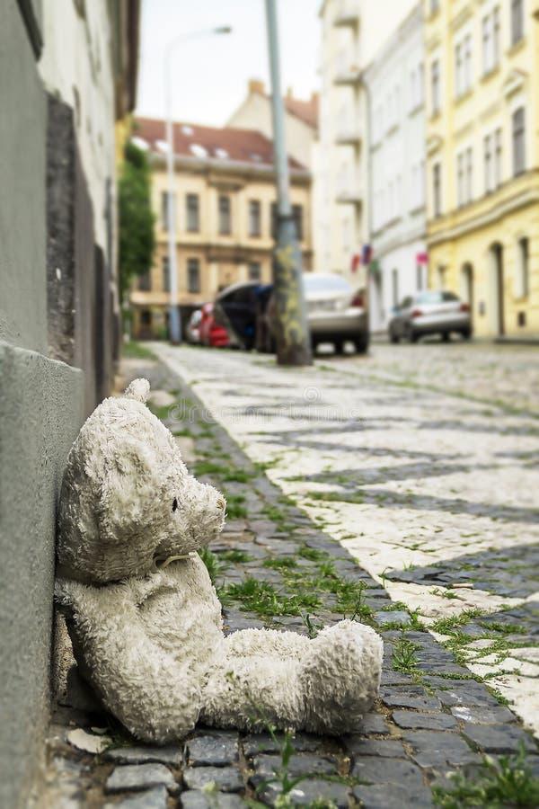 Oude teddybeer op de stoep stock fotografie