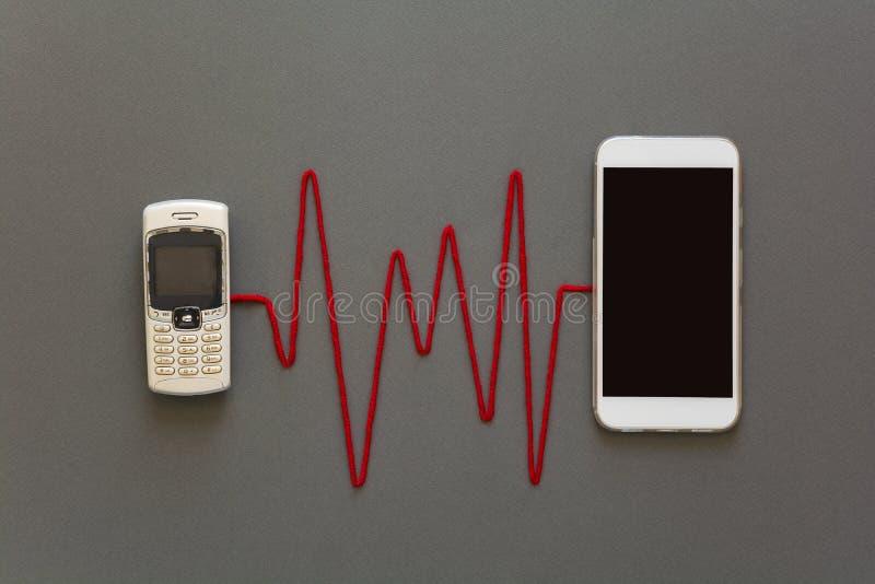 Oude telefoon en nieuwe die smartphone door rode impuls wordt aangesloten die op grijze document achtergrond leggen De technologi royalty-vrije stock foto's