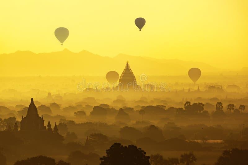 Oude tempel en hete lucht de ballon vliegt over hemel in Bagan na zonsopgang stock foto