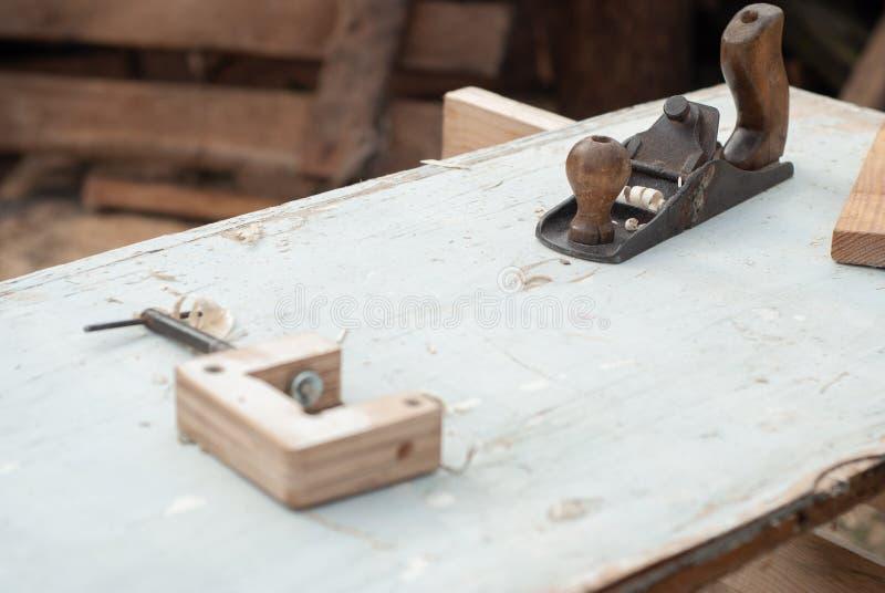 Oude timmerwerkhulpmiddelen De werkplaats van de timmerman openlucht, de hulpmiddelen van de timmerman op houten lijst, stock afbeeldingen