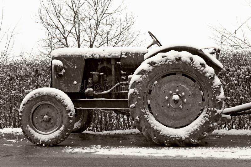 Oude tractor in de winter stock afbeeldingen