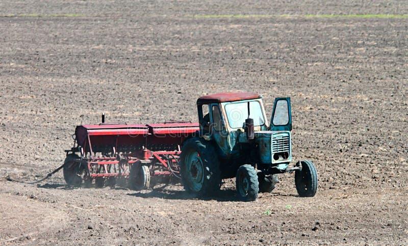 Oude tractor die op het gebied lopen royalty-vrije stock afbeelding