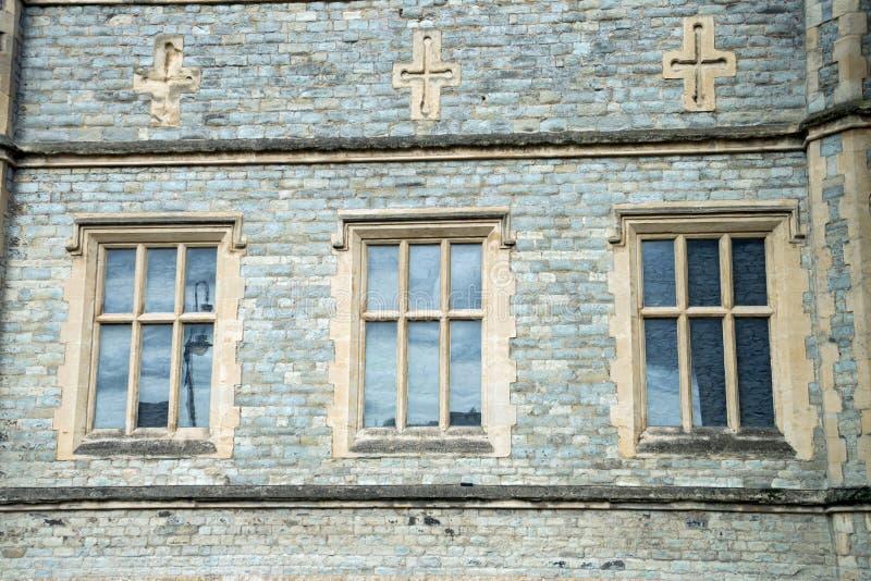 Oude traditionele Engelse Architectuur, drie vensters en kruisen hierboven royalty-vrije stock afbeeldingen