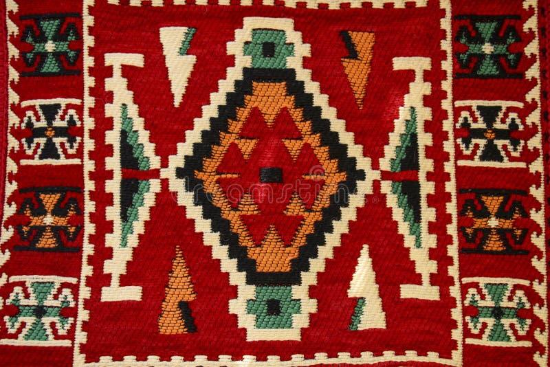 Oude traditionele tapijt met een geometrisch patroon donkerrood en wit in Arabische stijl op bazaar in Mostar, Bosnië en royalty-vrije stock foto