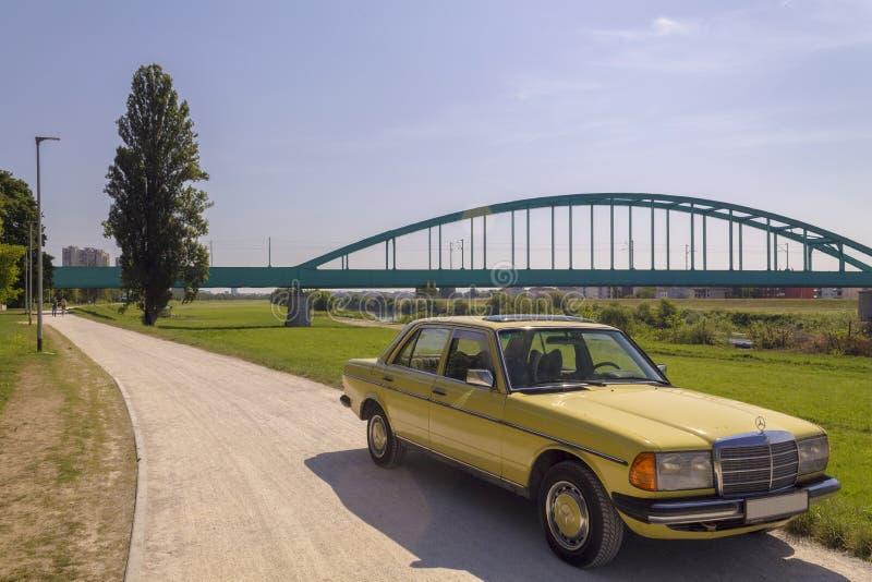 Oude uitstekende auto en een treinbrug stock fotografie