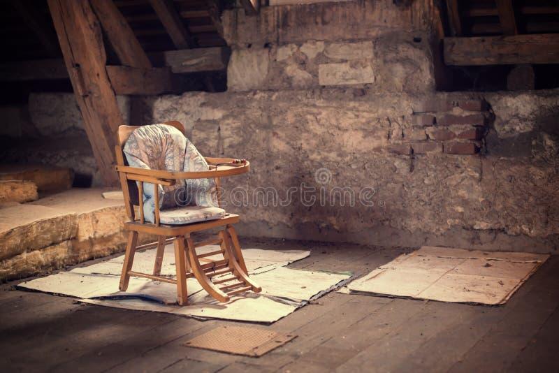 Oude uitstekende babystoel in een zolder stock afbeeldingen