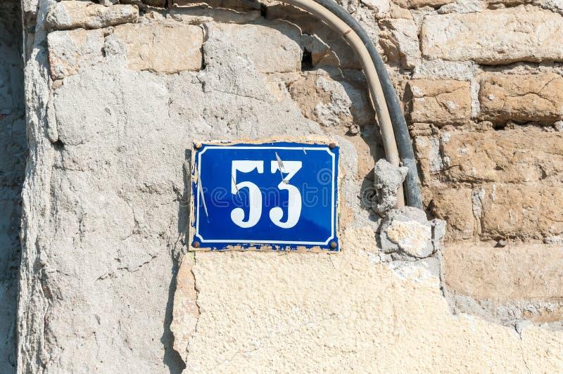 Oude uitstekende blauwe het metaalplaat nummer 53 drieënvijftig van het huisadres op de pleistervoorgevel van verlaten huis buite stock foto