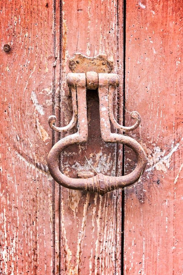 Oude uitstekende deurkloppers op een oude rode deur royalty-vrije stock fotografie