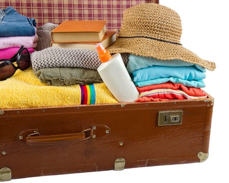 Oude uitstekende die koffer met kleren en vakantie wordt ingepakt accessorie stock foto