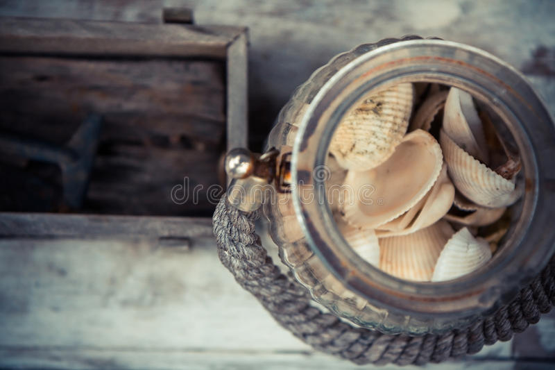 Oude uitstekende glaskruik met overzeese shells op vage houten achtergrond met copyspace Uitstekend tropisch stilleven stock foto