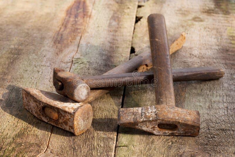 Oude uitstekende hamers op een houten achtergrond stock fotografie