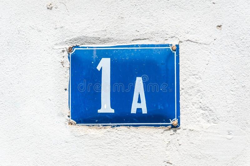 Oude uitstekende het metaalplaat nummer 1 A van het huisadres op de pleistervoorgevel van verlaten huis buitenmuur aan de straatk stock foto