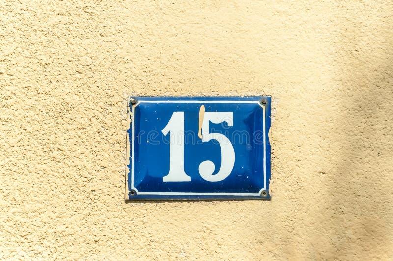 Oude uitstekende het metaalplaat nummer 15 vijftien van het huisadres op de pleistervoorgevel van verlaten huis buitenmuur aan de stock foto