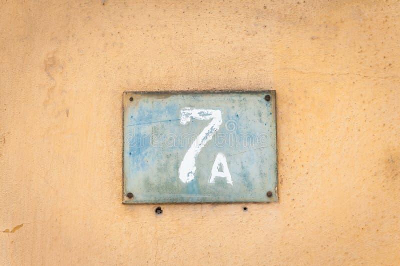 Oude uitstekende het metaalplaat nummer 7 A zeven van het huisadres op de pleistervoorgevel van verlaten huis buitenmuur aan de s royalty-vrije stock afbeelding