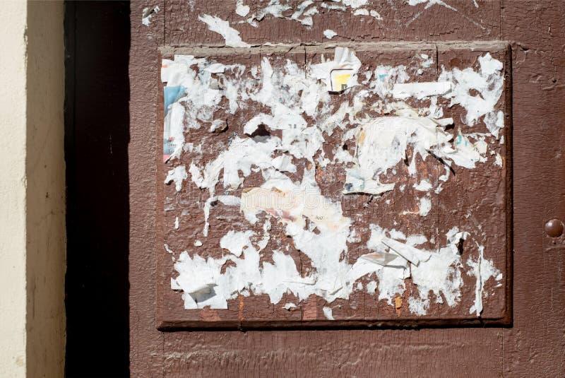 Oude uitstekende houten deur, resten van document en reclame op de deur Roodachtige Sinaasappel Gebarsten Verf royalty-vrije stock fotografie