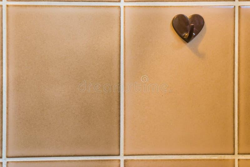 Oude uitstekende plastic hanger bij het retro betegelen in de badkamers, retro haak voor het hangen van de handdoek, de achtergro stock fotografie