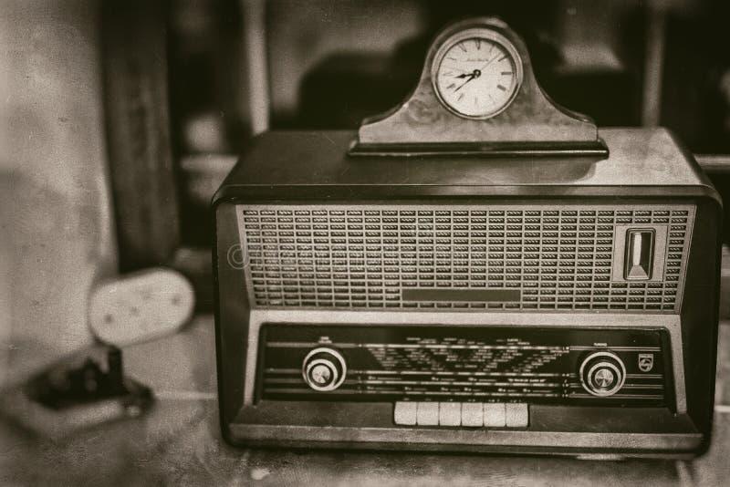 Oude uitstekende radioontvanger van de laatste eeuw met rustieke klok op bovenkant op venstervensterbank - vooraanzicht, sepia royalty-vrije stock foto's
