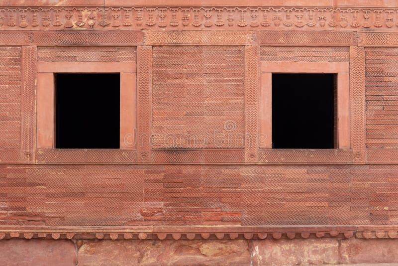Oude uitstekende rode bakstenen muur en twee vensters in Fatehpur Sikri Pal royalty-vrije stock fotografie