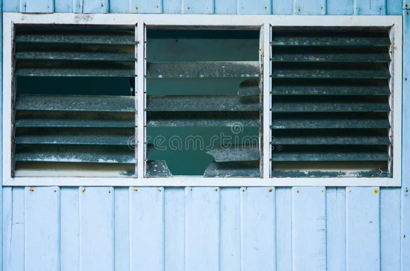 Oude uitstekende schuur met en gebroken venster stock afbeelding