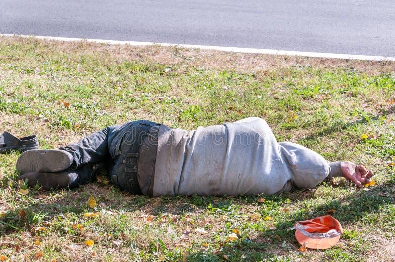 Oude van de vuile gedronken of drugverslaafde blootvoetse daklozen of vluchteling mensenslaap op het gras in het straat sociale d royalty-vrije stock afbeelding
