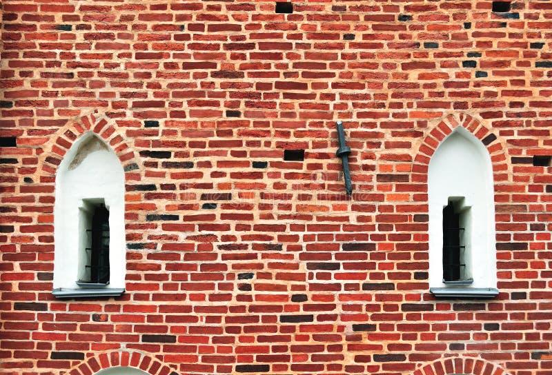Oude vensters op een rode bakstenen muur stock fotografie