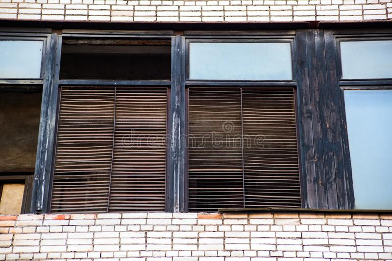 Oude vensters van een baksteengebouw met jaloezie stock afbeelding