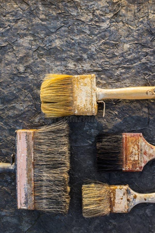 Oude verfborstels op een steenoppervlakte royalty-vrije stock afbeelding