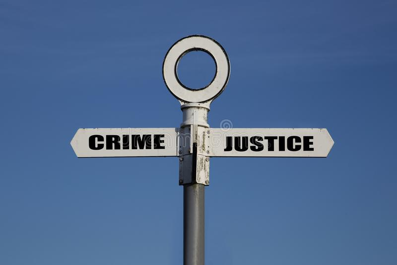 Oude verkeersteken met misdaad en rechtvaardigheid die in tegenovergestelde richtingen wijzen stock foto's