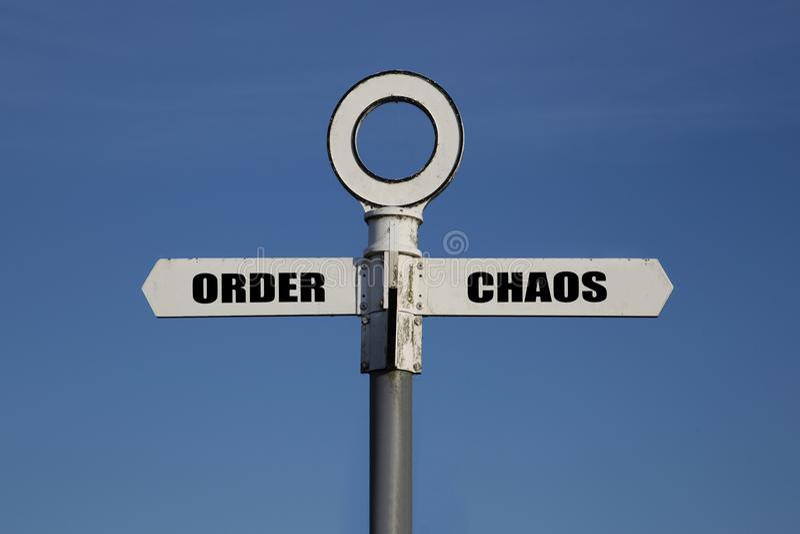 Oude verkeersteken met orde en chaos die in tegenovergestelde richtingen wijzen stock afbeelding