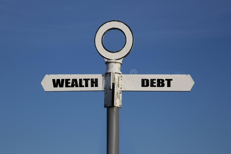 Oude verkeersteken met rijkdom en schuld die in tegenovergestelde richtingen wijzen royalty-vrije stock foto