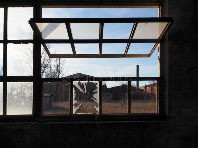 Oude verlaten die fabriek door een half open venster wordt bekeken stock afbeeldingen