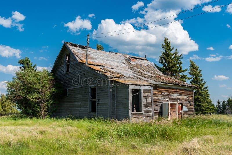 Oude verlaten die prairieboerderij door bomen, lang gras en blauwe hemel wordt omringd stock foto's