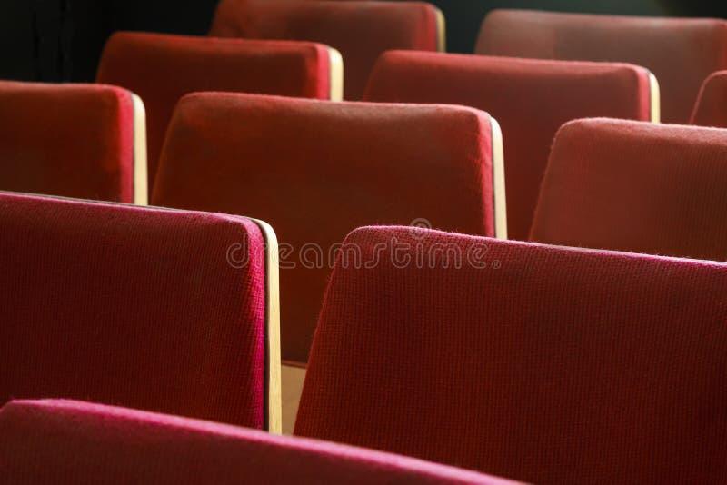 Oude vermoeide die bioskoopzetels met versleten rood fluweel worden behandeld Lege rode stoelen in theater Rode theaterzetels stock foto's