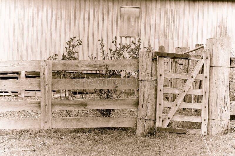 Oude vermoeide landbouwbedrijfpoort in sepia stock foto's