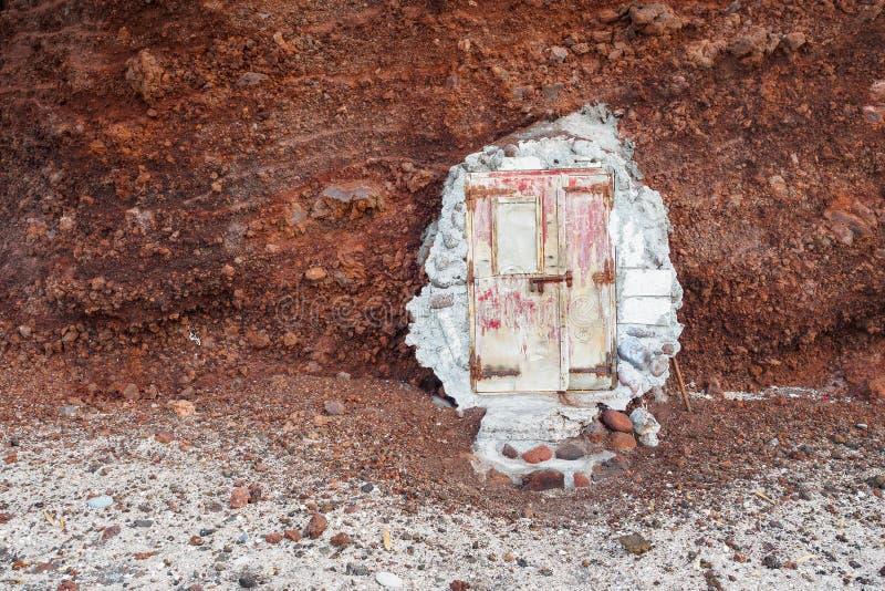 Oude versleten deur aan de rode rots stock afbeelding