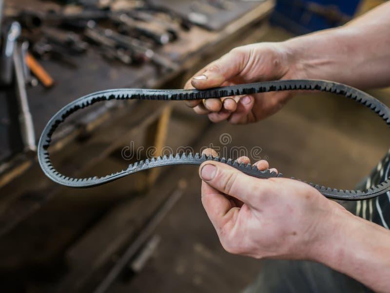 Oude versleten rubberalternatorriem in de handen van mensen Het concept autoonderhoud De ruimte van het exemplaar stock foto's