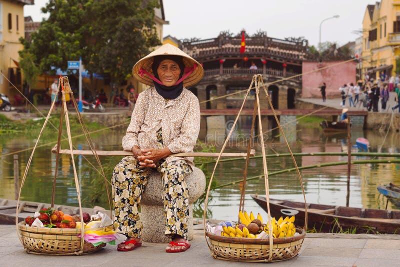 Oude Vietnamese Fruitverkoper in Hoi An, Vietnam stock afbeeldingen
