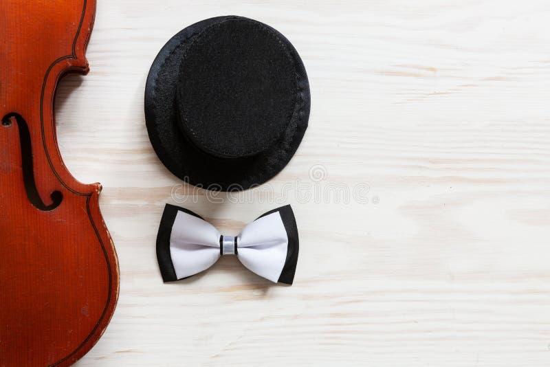 Oude viool, cilinderhoed en vlinderdas op de witte houten achtergrond Hoogste mening, close-up royalty-vrije stock afbeelding