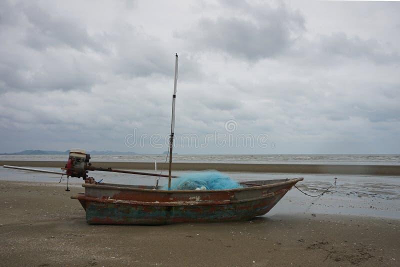 Oude vissersboot met blauw visnet op nat stock fotografie