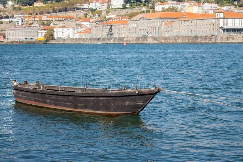 Oude vissersboot op de Douro in Porto, Portugal Bruine retroboot tegen Porto-dijk met gebouwen stock foto's