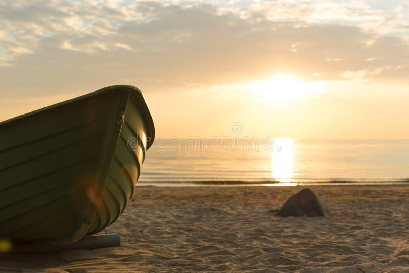 Oude vissersboot in zonsondergangtijd Zonsondergang bij de Oostzee Beac stock afbeelding