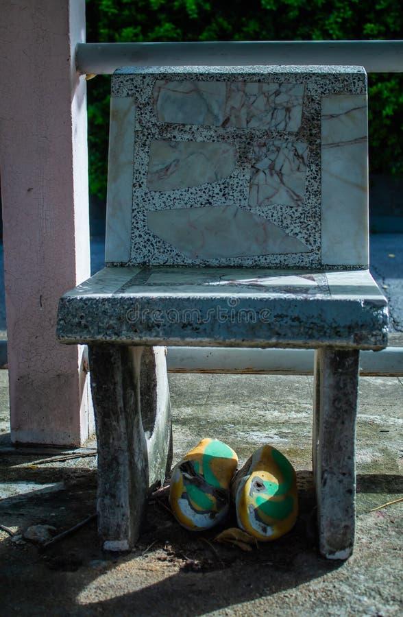 Oude voetbalschoenen gebroken onder de stoelrots royalty-vrije stock afbeelding