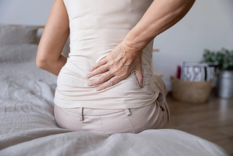Oude, volwassen vrouw op bed aanraken voelt rugpijn stock fotografie