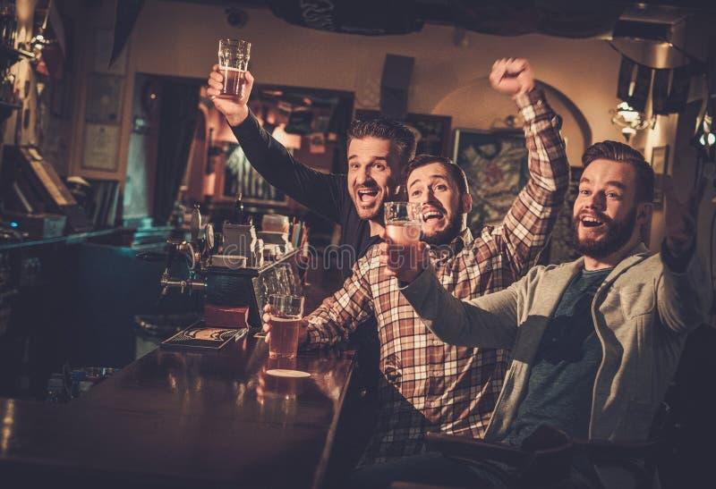 Oude vrienden die pret hebben die op een voetbalspel op TV letten en ontwerpbier drinken bij barteller in bar royalty-vrije stock foto's