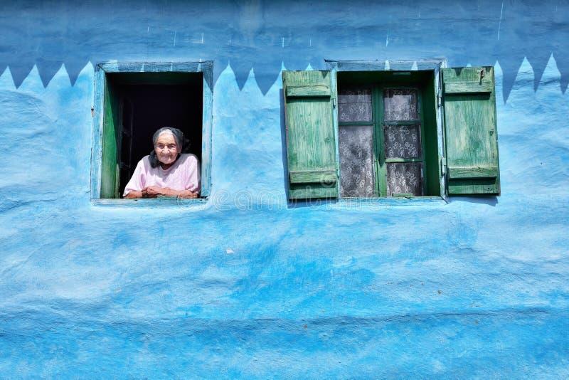 Oude vrouw bij het venster in oud traditioneel blauw huis stock afbeelding