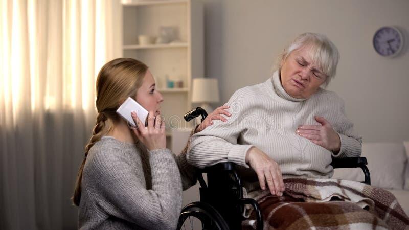Oude vrouw die aan hartaanval, kleindochter lijden die ziekenwagen, gezondheid roepen royalty-vrije stock foto