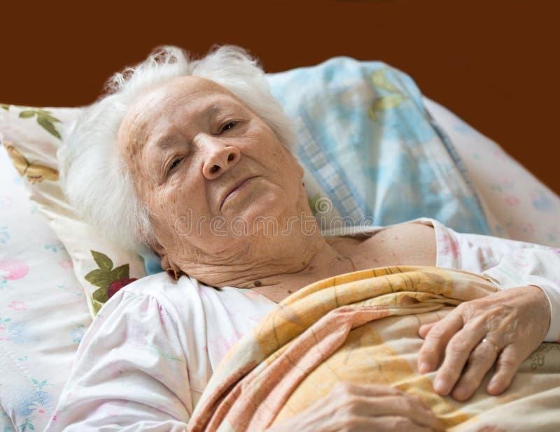 Oude vrouw die bij bed leggen stock afbeelding