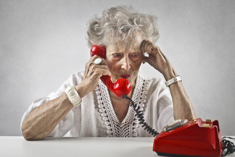 Oude vrouw die bij een uitstekende telefoon spreken royalty-vrije stock afbeeldingen