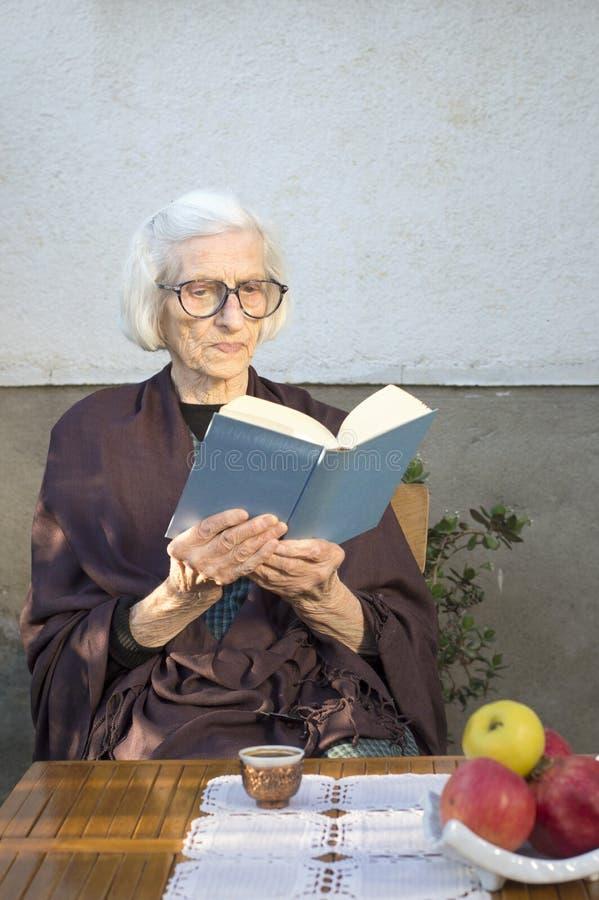 Oude vrouw die een boek in de binnenplaats lezen royalty-vrije stock foto