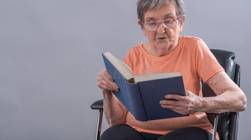 Oude vrouw die een boek lezen royalty-vrije stock afbeeldingen